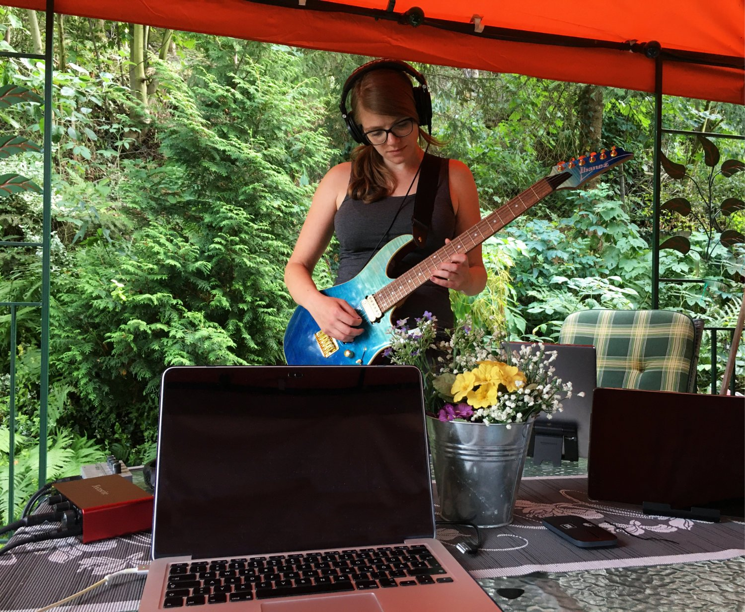 Anja playing a blue guitar in the garden